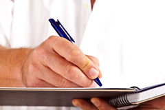 Man writing in a book Stock Photography
