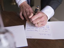 Man writing card. Left handed man wearing tuxedo and ring is writing card. Wedding concept Royalty Free Stock Image