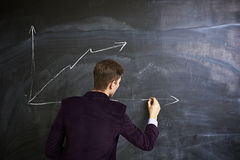 Man writing on the chalkboard. Young student draws a graph on the chalkboard Stock Photography