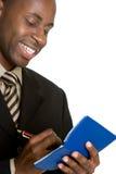 Man Writing Check. Smiling black man writing check Royalty Free Stock Photo