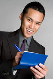 Man Writing Check. Asian business man writing check Royalty Free Stock Images