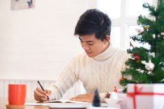 Man writing christmas and new year greeting cards. Man writing greeting cards at home during christmas and new year royalty free stock photos