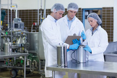 Man writing on clipboard while colleagues testing product. In the factory Stock Photo