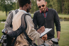 Man writing in clipboard while looking on two golf players. African american men writing in clipboard while looking on two golf players Stock Photos