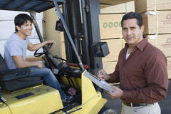 Man Writing On A Clipboard With Worker Driving Forktruck At Warehouse Royalty Free Stock Photos