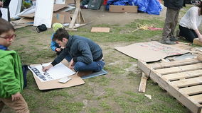 Man writing Come to Nuit de Debout during 'Nuit Debout' stock footage