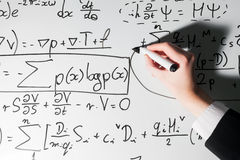 Man writing complex math formulas on whiteboard. Mathematics and science Stock Photo