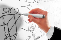 Man writing complex math formulas on whiteboard. Mathematics and science Stock Image