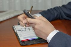 Man checking appointment on personal organizer schedule. Man writing contact list from mobile phone into her business agenda notebook for backup Royalty Free Stock Images