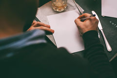Man writing contract on table. In cafe Stock Image