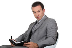 Man writing in diary. Man in suit writing in diary Stock Image