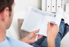 Man Writing In Diary Royalty Free Stock Image