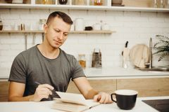 Man writing in diary drinking morning coffee. Inspiration, deadline, day planning, lifestyle, early awake. man writing in diary drinking morning coffee at home royalty free stock images