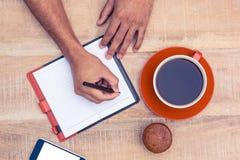 Man writing on diary Stock Image