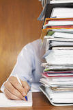 Man Writing Document Behind A Stack Of Folders Royalty Free Stock Photography