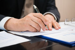 Man writing on a document. Detail of a businessman writing on a document Stock Photo