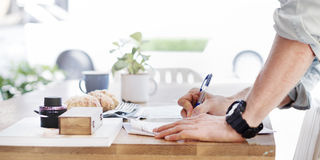Man Writing Document Dinning Table Concept Stock Image