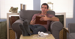 Man writing down notes in book. Man sitting on couch and writing down notes in book Stock Photos