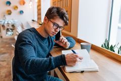 Man writing down something in notebook while talking on mobile phone at cafe Stock Photos