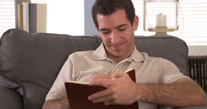 Man writing down thoughts in journal Stock Images