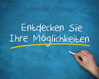 Man writing entdecken sie ihre moglichkeiten with a chalk Royalty Free Stock Photo