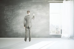 Man writing formulas on wall. Businessman writing mathematical formulas on chalkboard wall in room with concrete floor, window with curtain and city view. 3D Royalty Free Stock Images