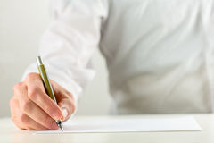 Man writing with a fountain pen on blank paper. Close up of the hand of a man writing with a fountain pen on a sheet of blank white paper or document in a stock images