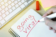 Man writing going viral in a note. Man writing going viral in a note pad Royalty Free Stock Image