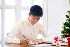 Man writing christmas and new year greeting cards. Man writing greeting cards at home during christmas and new year royalty free stock image