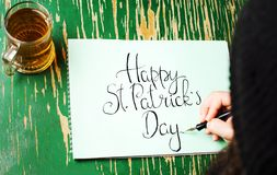Man writing a Happy St Patrick day card. Man writing a Happy St Patrick day calligraphy card Royalty Free Stock Photography