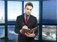 Man writing on his agenda. Portrait of a young man writing on his agenda Royalty Free Stock Images