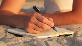Man writing in his diary at the beach. While lying on the golden sand, close up view of the book and his hand holding a pen Shot on Canon 5D Mark II with Prime stock footage