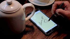 Man writing I love you inscription on the smart phone screen stock video