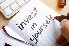 Man is writing invest in yourself. Man is writing invest in yourself in a note royalty free stock images
