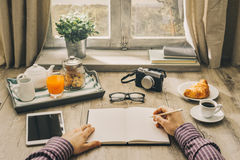 Man writing a journal. Hipster man having a tasty breakfast at home on a vintage table in front of a window, he is writing on a notebook, point of view shot royalty free stock image