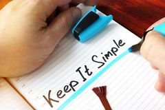 Man writing Keep IT Simple. Man writing Keep IT Simple in the note Royalty Free Stock Images