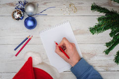 Man writing letter to Santa in Christmas situation Stock Images