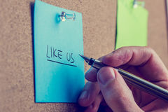 Man writing - Like Us - on a notice board. Man writing - Like Us - on a blue note notice board in a request for followers on social media sites and networks royalty free stock images