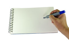 Man writing with a marker on a spiral bound book. Man writing with a blue felt tip marker pen on a blank white spiral bound book holding the pen in his hand Stock Photo