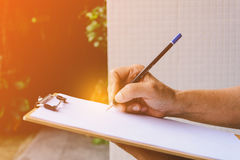 Man writing a message on it paper on clipboard Stock Photography