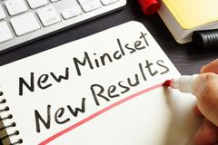 Man is writing New Mindset New Results. Man is writing New Mindset New Results in a note royalty free stock photos