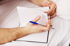 Man writing a note in bed. Handsome man writing a note in bed Stock Image