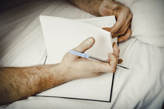 Man writing a note in bed. Handsome man writing a note in bed Stock Images