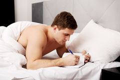 Man writing a note in his bed. Stock Photography