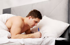 Man writing a note in his bed. Royalty Free Stock Images