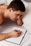 Man writing a note in his bed. Stock Photo