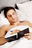 Man writing a note in his bed. Handsome man writing a note in his bedroom on bed Royalty Free Stock Photos
