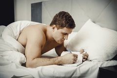 Man writing a note in his bed. Handsome man writing a note in his bedroom on bed Stock Photo