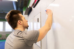 Man writing note to whiteboard in gym. Sport, fitness and people concept - man writing note to whiteboard in gym Stock Photography