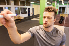 Man writing note to whiteboard in gym. Sport, fitness and people concept - man writing note to whiteboard in gym Royalty Free Stock Images